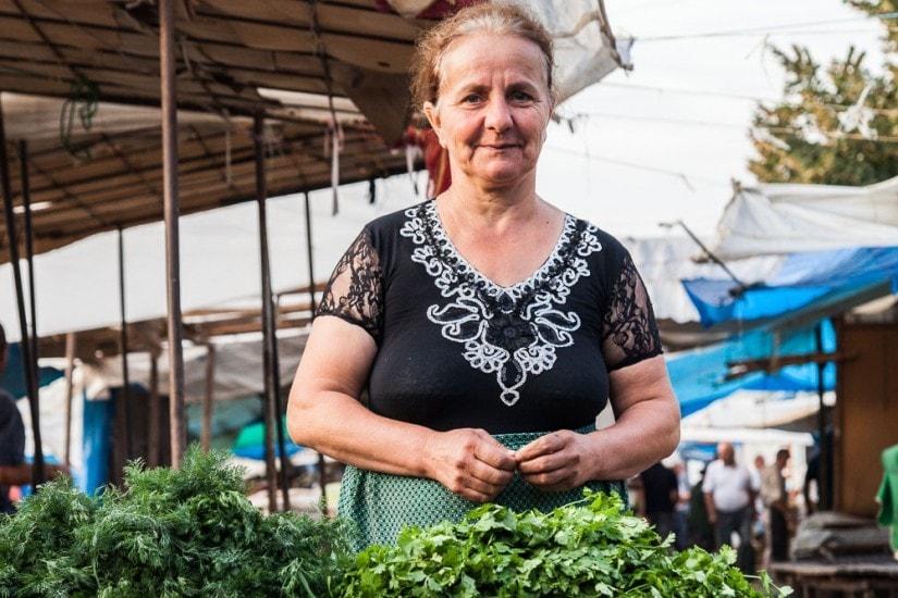 Frau verkauft an ihrem Marktstand frische Kreuter.