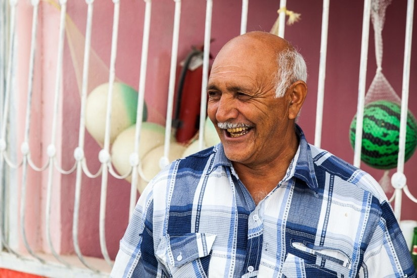 älterer lachender Mann mit Goldzähnen.