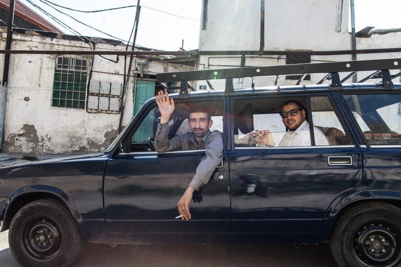 Zwei rauchende und winkende Männer in einem blauen Auto irgendwo in Baku.