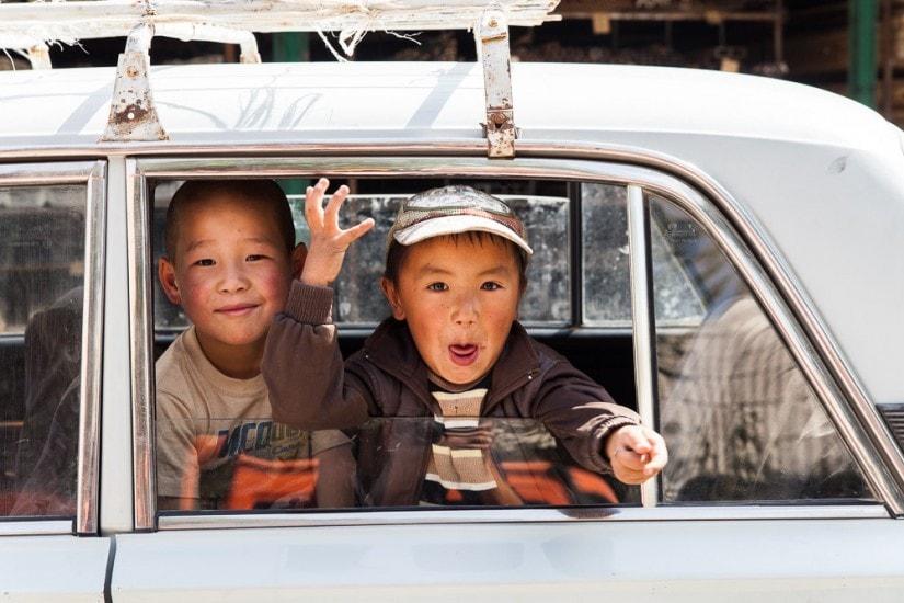Zwei kirgisische Jungen schauen aus einem Auto.