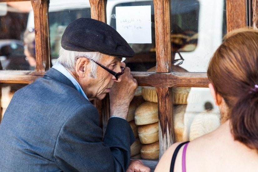 Alter Mann mit Mütze und Brille wartet vor einer Bäckerei bis diese öffnet.