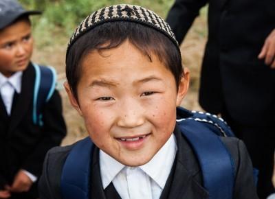 Porträt von einem girgisischen Jungen in Schuhluniform.