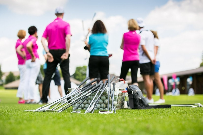Golfer stehen im Kreis und lassen sich etwas erklären.