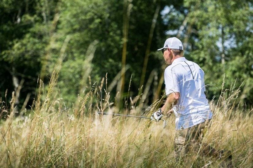 Mann sucht im hohen Gras seinen Golfball.