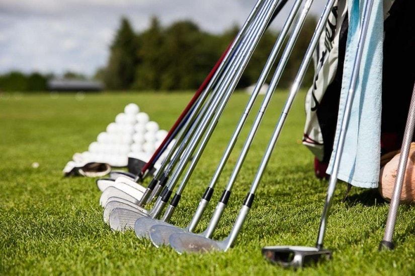 Aufgereihte Golfgschläger, im Hintergrund eine Pyramide aus Golfbällen.