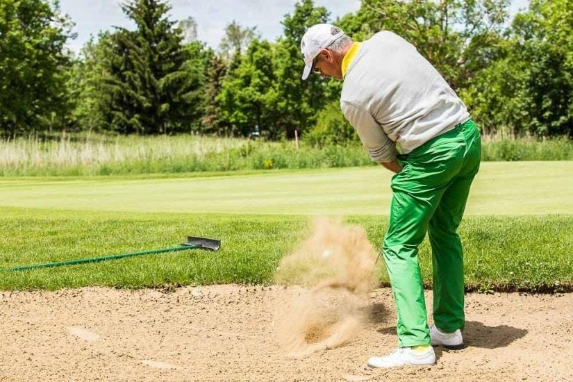 Mann schlägt Golfball aus einem Bunker.