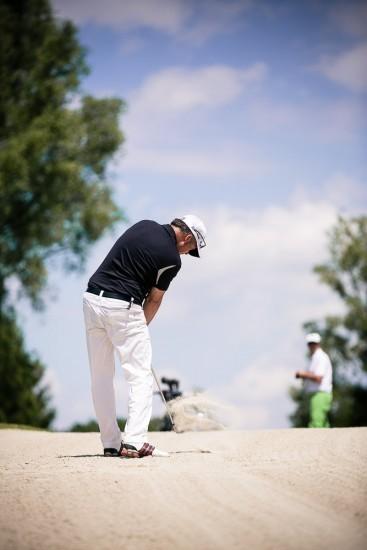 Mann schlägt Golfball aus einen Bunker.