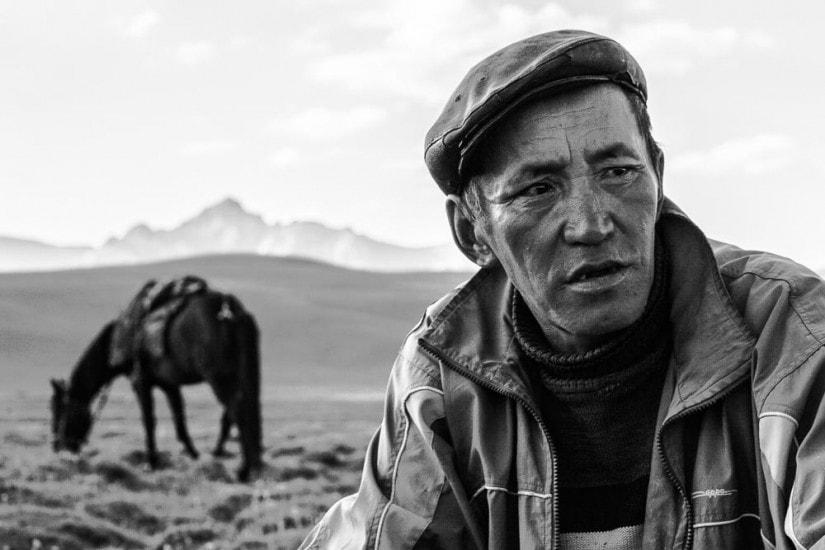 Porträt von einem Kirgisen, im Hintergrund steht sein Pferd.