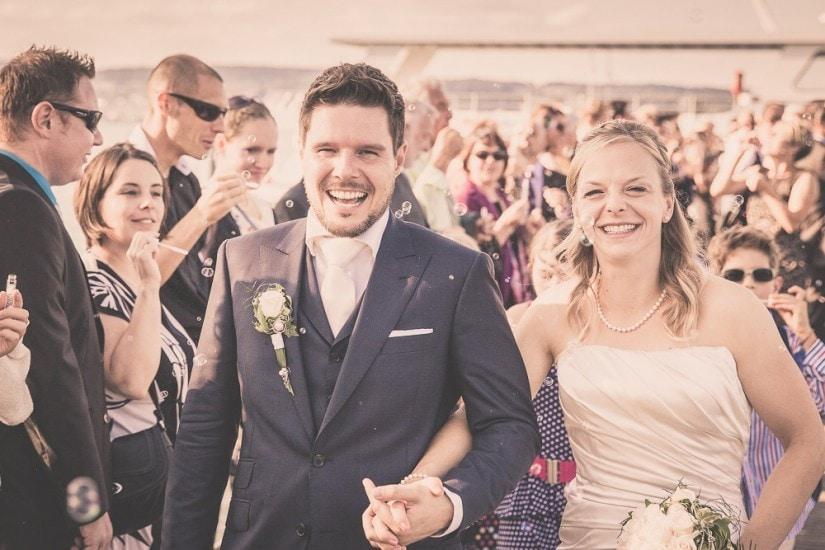 Hochzeitspaar läuft durch Menschenmasse.