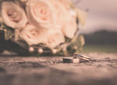 Makroaufnahme von zwei Ringen, im Hintergrund verschwommen der Brautstrauss.