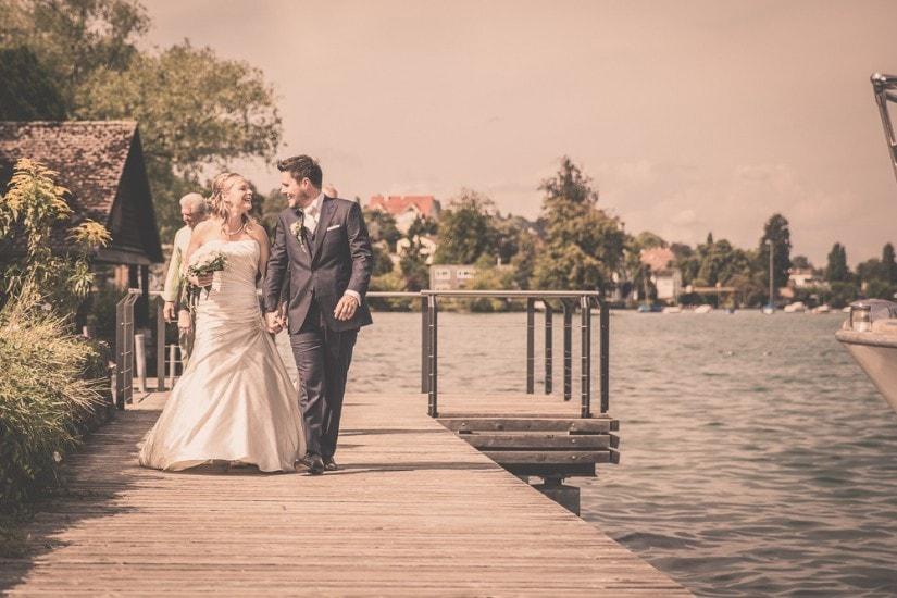 Hochzeitspaar läuft auf einem Steg.