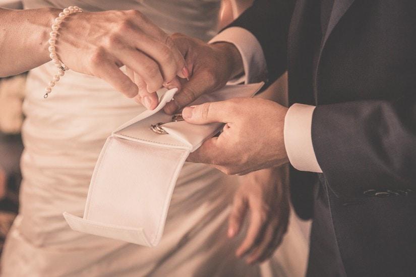 Hände packen Hochzeitsringe aus.