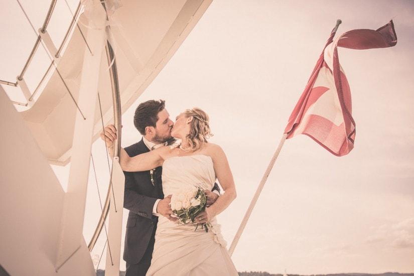Brautpaar küsst sich auf einem Schiff, Schweizerfahne weht im Hintergrund.