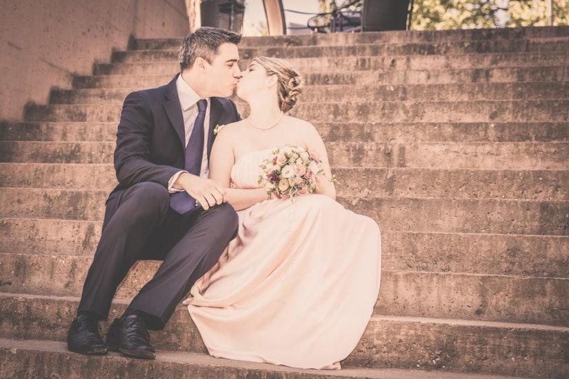 Brautpaar sitzt auf einer Treppe und küsst sich.