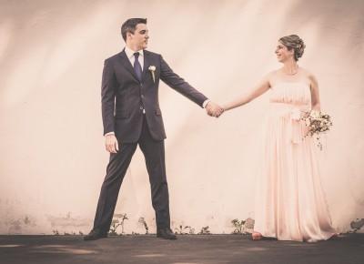 Brautpaar vor einer Mauer halten sich die Hände.