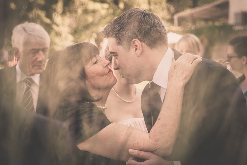 Mutter küsst Bräutigam.