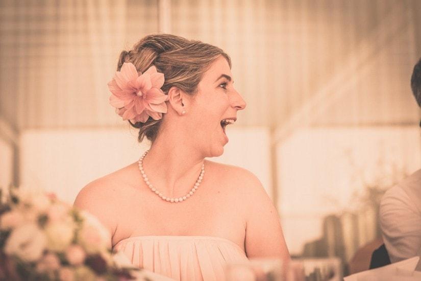 lachende Braut mit Perlenkette und Kopfschmuck.