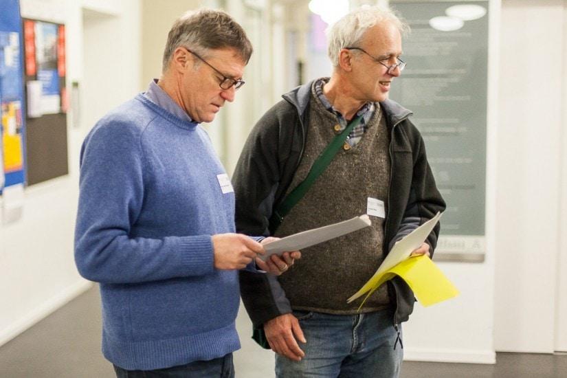 Zwei Männer mit Papierblätter in der Hand.