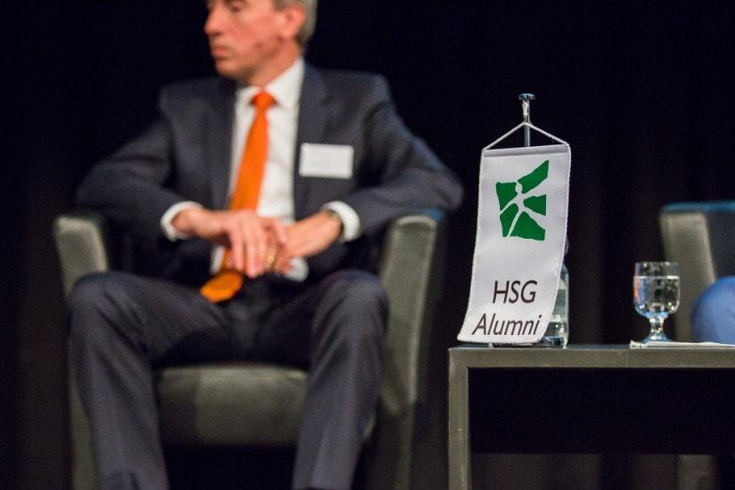 HSG Alumni Wimpel, im Hintergrund sitzt ein Mann mit oranger Krawatte.