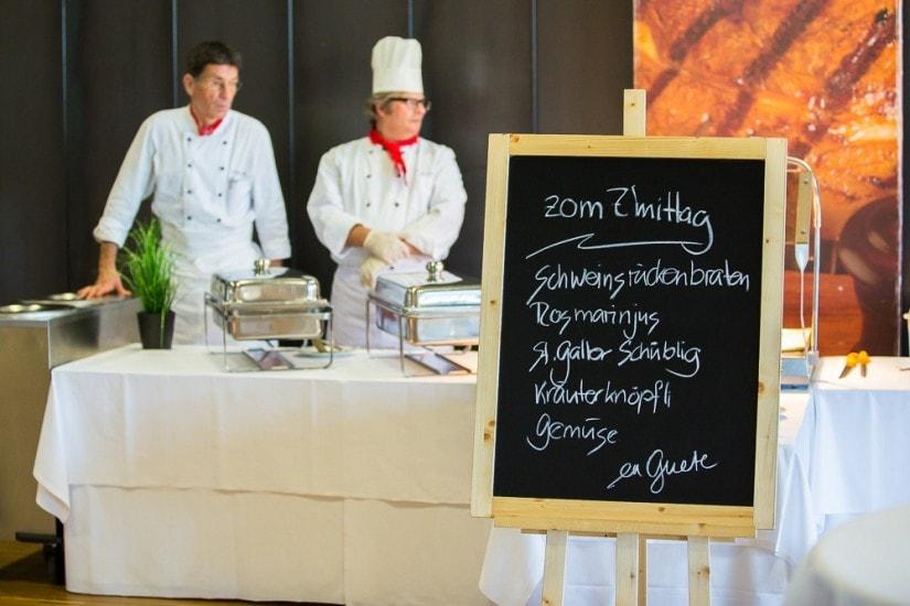 Tafel mit Mittasmenu, im Hintergrund stehen die Köche.