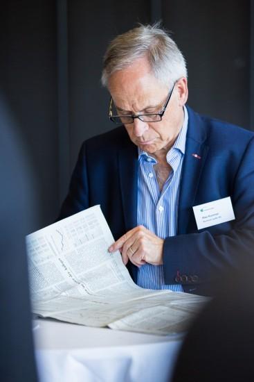 Mann mit Brille liest Zeitung.