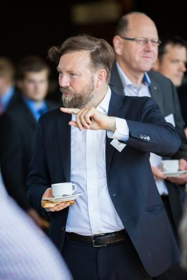 bärtiger Mann mit Kaffeetasse in der Hand.
