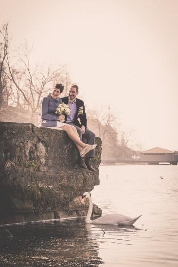 Brautpaar sitzt auf auf einer Mauer am Wasser, im Vordergrund schwimmt ein Schwan.