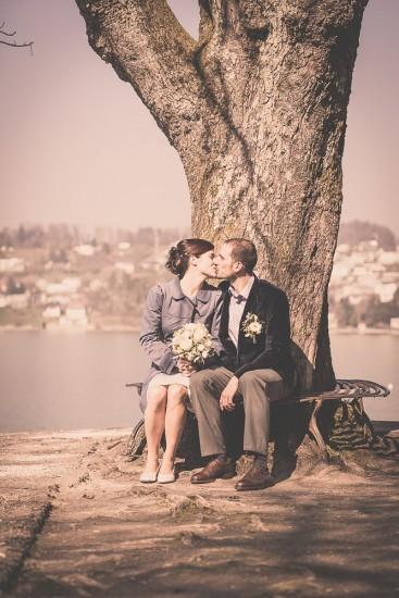 Brautpaar sitzt auf einem Bank und küsst sich.