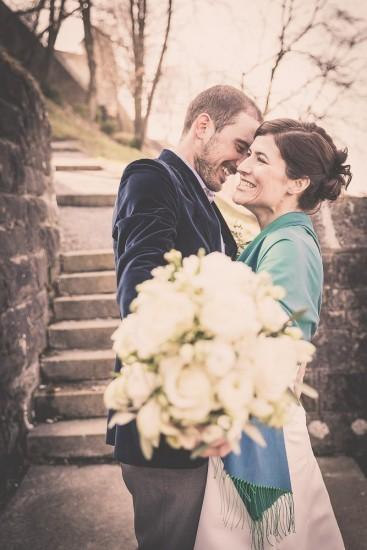 verliebtes lachendes Brautpaar auf einer Treppe.