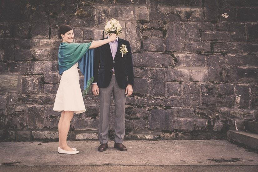 Paar steht vor einer Mauer, Braut hält Bräutigam den Brautstrauss vor das Gesicht.