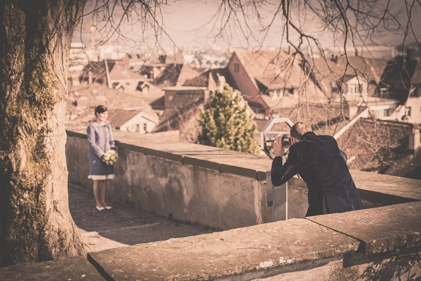Bräutigam schaut mit Feldstecher Richtung Braut.