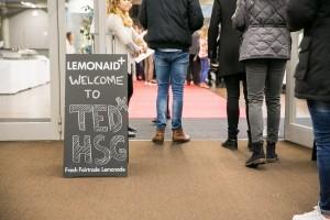 Welcome Plakat und Personen beim Eingang.