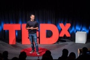 """Mann namens """"Phil Anthony M"""" auf der TEDx Bühne."""