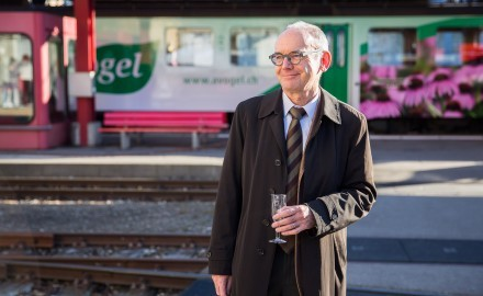 """Mann namens """"Robert Baldinger"""" vor einer Lok der Appenzeller Bahnen mit A.Vogel Werbung."""