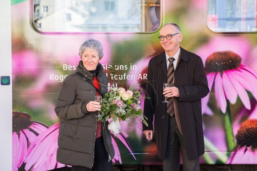 """Mann namens """"Robert Baldinger"""" mit seiner Frau vor einer Lok der Appenzeller Bahnen mit A.Vogel Werbung."""