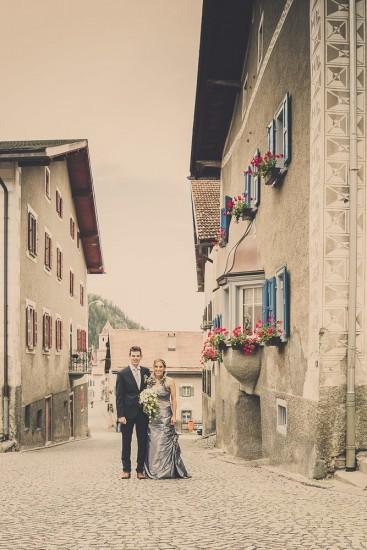 Hochzeitspaar steht in einer engen Gasse im Dorf Bergün.