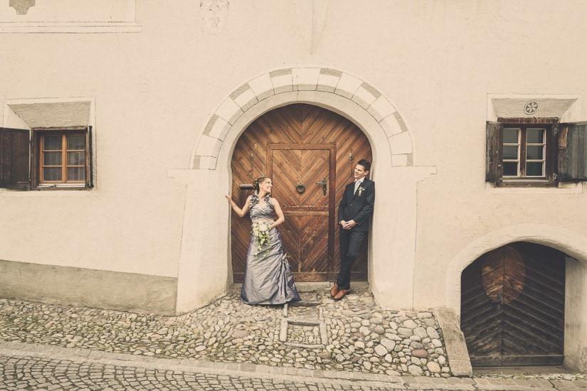 Brautpaar steht vor einer grossen, schweren und alten Holztür.