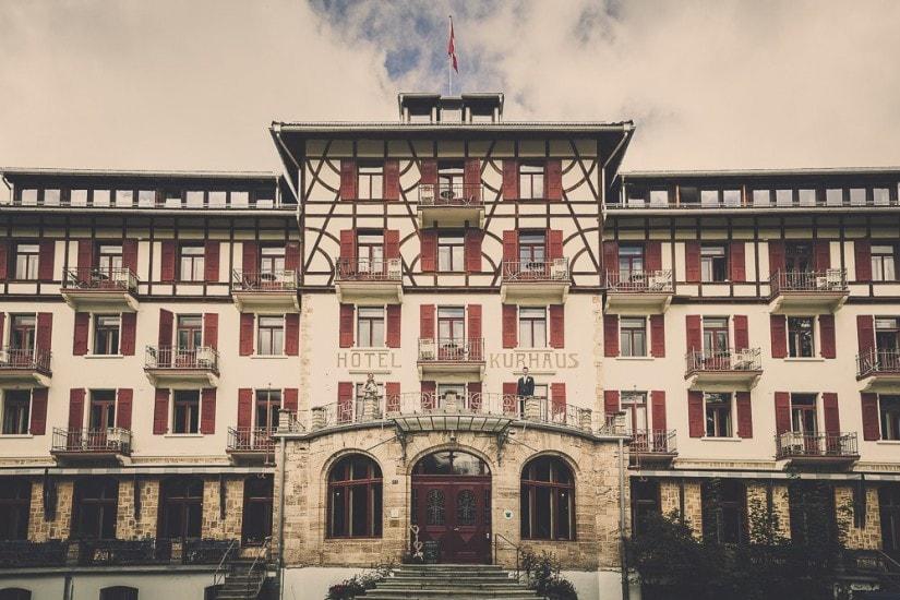 Brautpaar steht auf der grossen Terrasse vom Hotel Kurhaus Bergün.