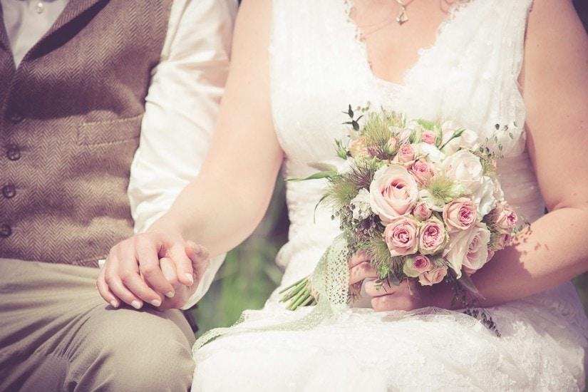 Nahaufnahme von Händen und Brautstrauß