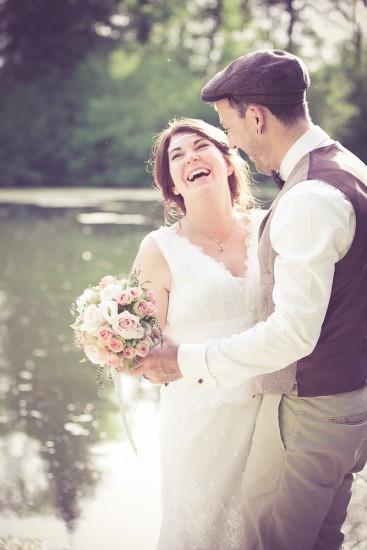 tanzendes Brautpaar ein einem Gewässer mit Rosentrauss in der Hand.