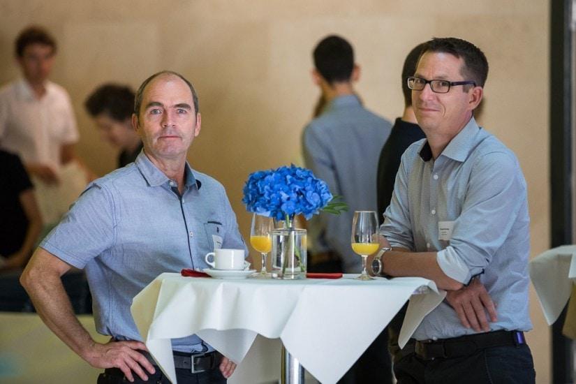 Zwei Männer an einem Bistrotisch.