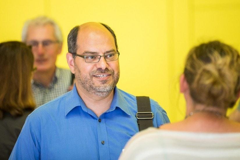 Mann mit blauem Hemd und Brille.