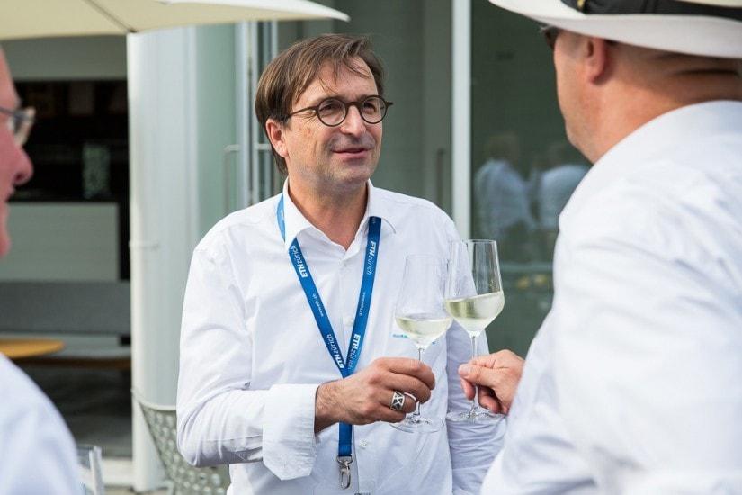 Zwei Männer prosten sich mit Weissweingläser zu.