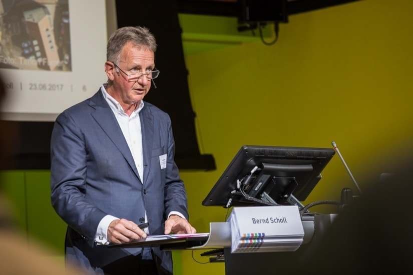 """Mann namens """"Bernd Scholl"""" auf einem Podium."""