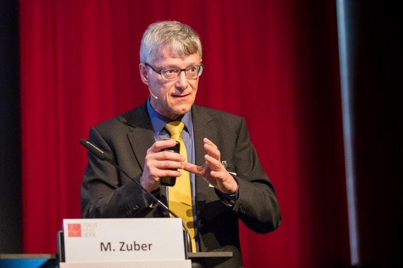 Mann am Podium spricht in ein Mikrofon.