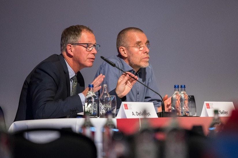Zwei Männer sitzen auf einer Bühne.