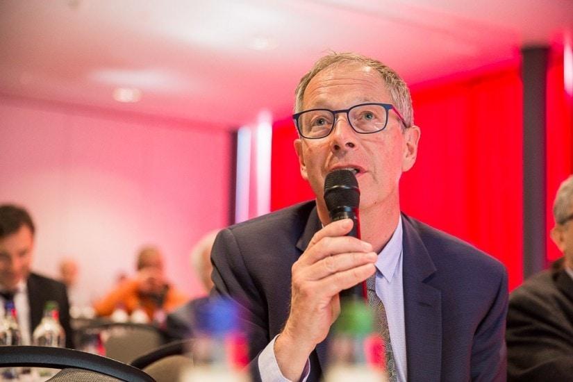 Mann mit Brille spricht in ein Mikrofon.