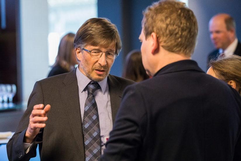 Mann mit Brille und Krawatte spricht mit einer anderen Person.