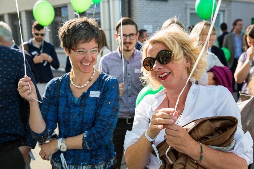 zwei fröhliche Frauen mit grünen Luftballons.