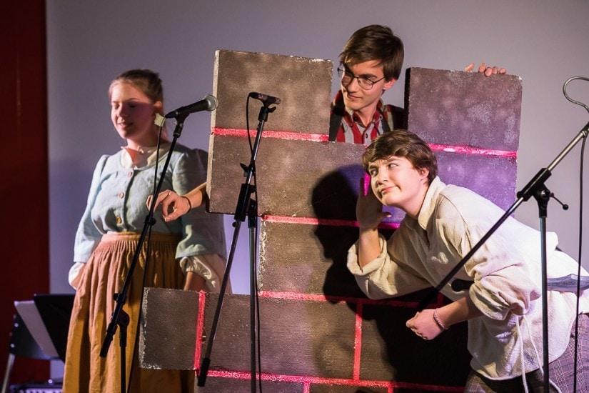 Theatervorstellung, Frau horcht an einer Mauer.